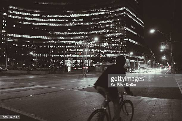 Rear View Of Person Riding Bicycle On Street Against Illuminated Building