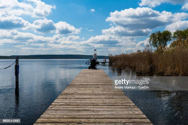Rear View Of Person Sitting On Pier At Lake Against Cloudy Sky