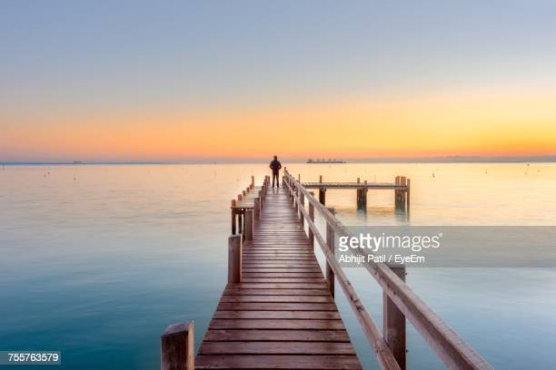 Rear View Of Person Standing On Pier Against Clear Sky During Sunset