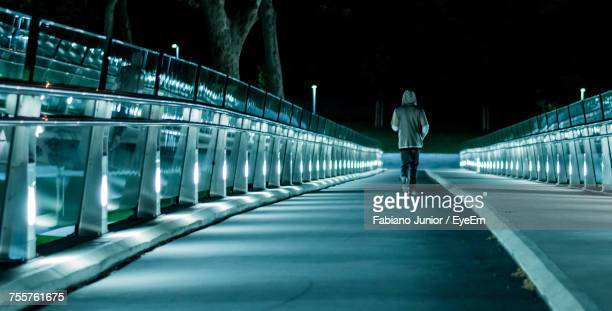 Rear View Of Person Walking On Illuminated Bridge At Night