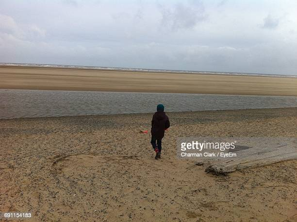 Rear View Of Person Walking On Sand At Beach Against Sky