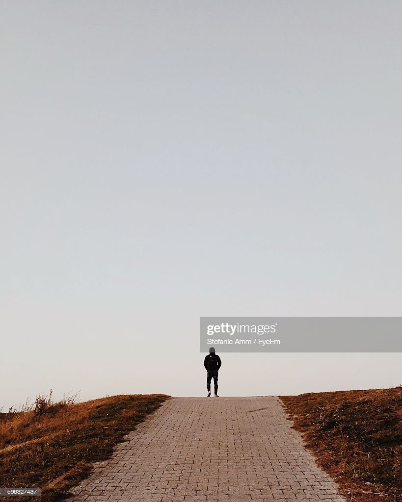 Rear View Of Person Walking On Street Against Sky