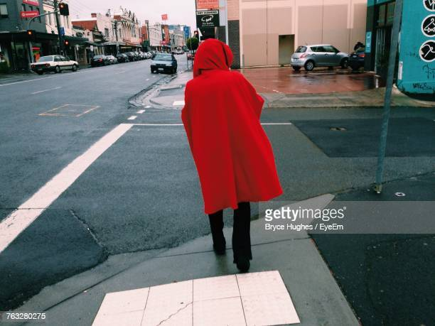 Rear View Of Person Wearing Red Jacket Crossing Road In City