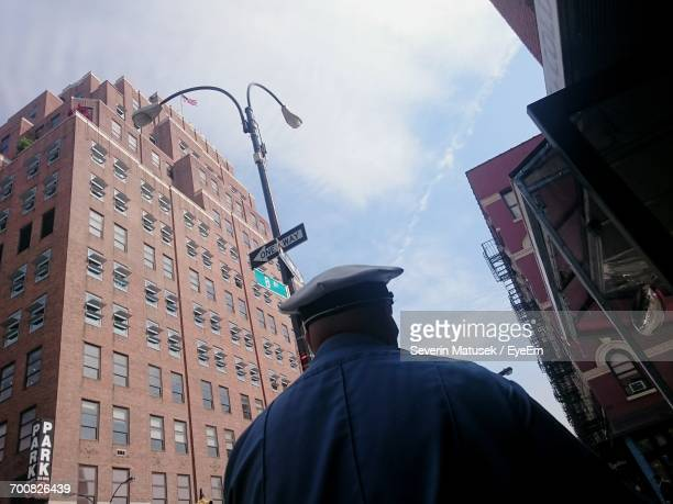 Rear View Of Policeman Against 111 Eighth Avenue