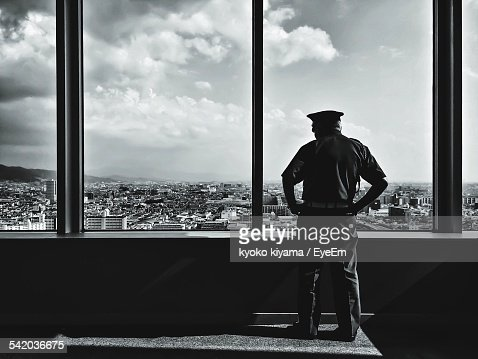 Rear View Of Policeman Looking At Cityscape Through Window