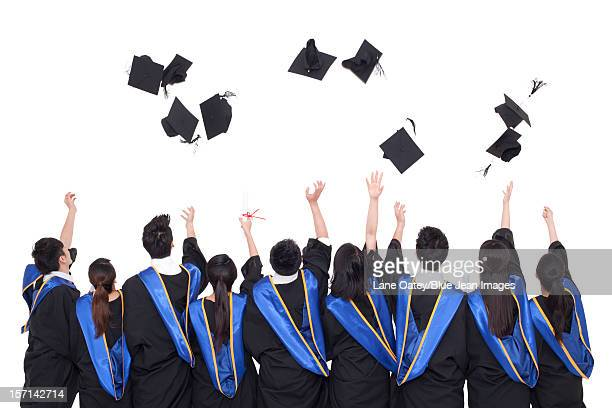 Rear view of Portrait of graduates throwing mortar boards