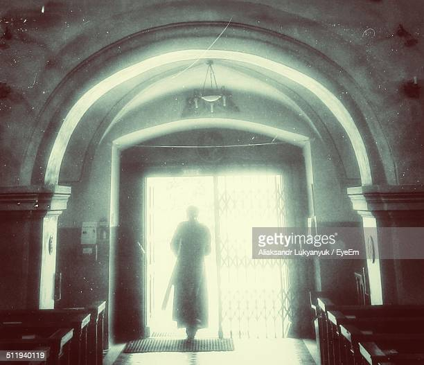 Rear view of priest exiting church