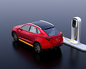Rear view of red electric SUV car charging in charging station. 3D rendering image.