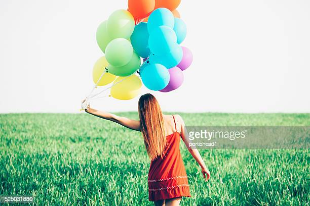 Rear view of redheaded woman with balloons in grassland