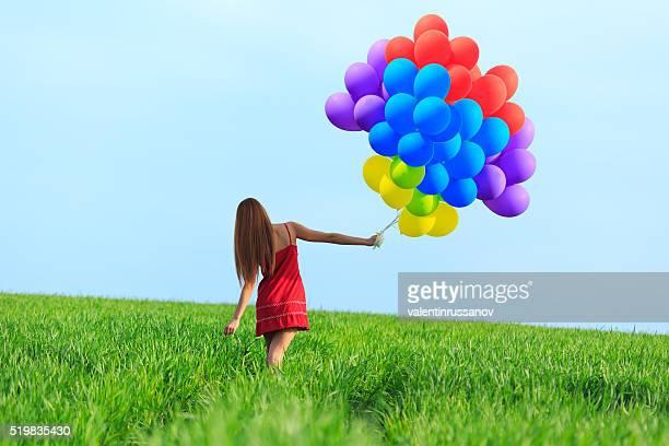 Rückansicht des junge Frau Tanzen mit roten Haaren mit bunten Luftballons