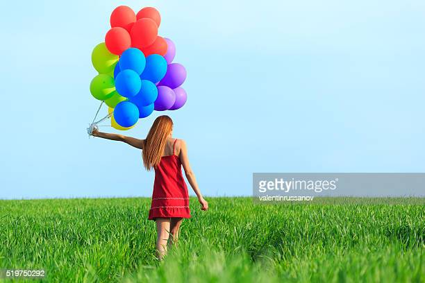Rear view of redheaded young woman with colored balloons