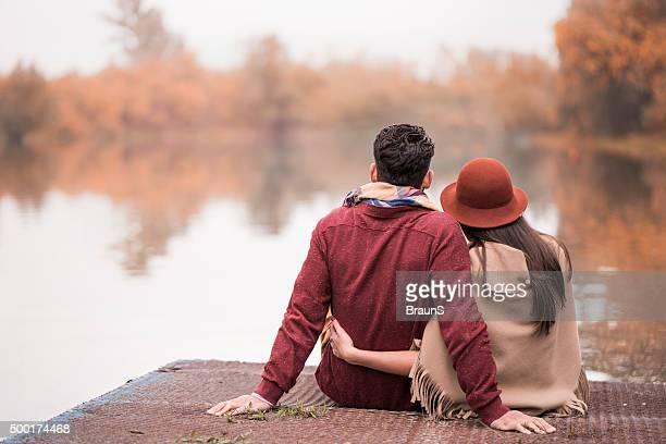 Vista traseira de um casal romântico em um cais no Outono.