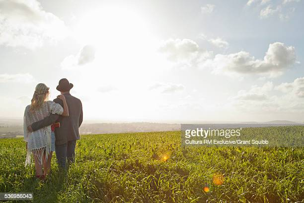 Rear view of romantic young couple in grassy field, Dorset England