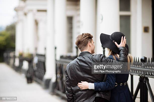 Rear view of romantic young couple strolling on street, London, England, UK
