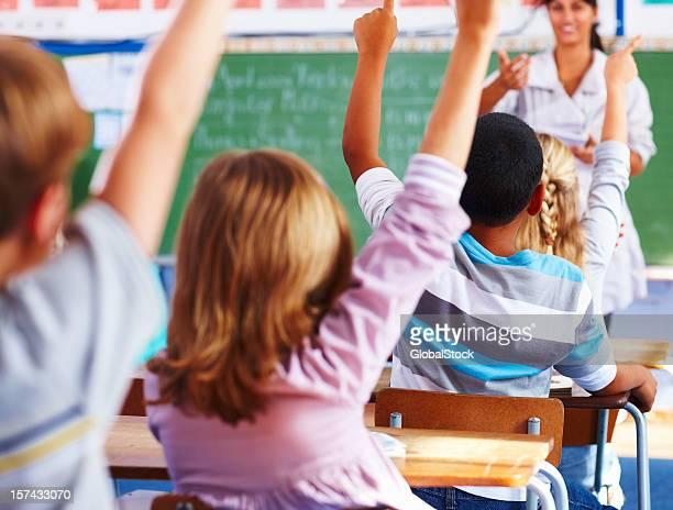 Vue arrière de l'école enfants pose ses mains