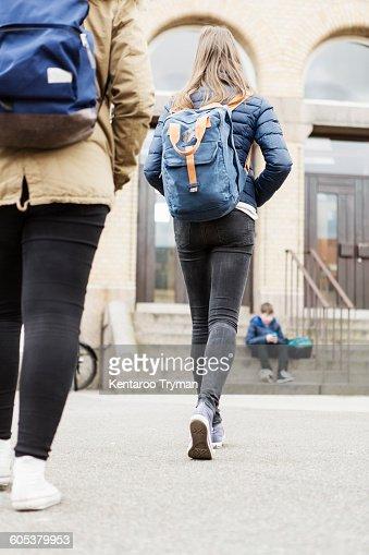 Rear view of schoolgirls walking towards school building