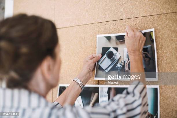 Rear view of senior businesswoman pinning photograph on bulletin board in portable office truck