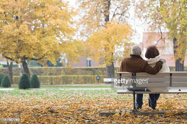 Rear view of senior couple on park bench in autumn