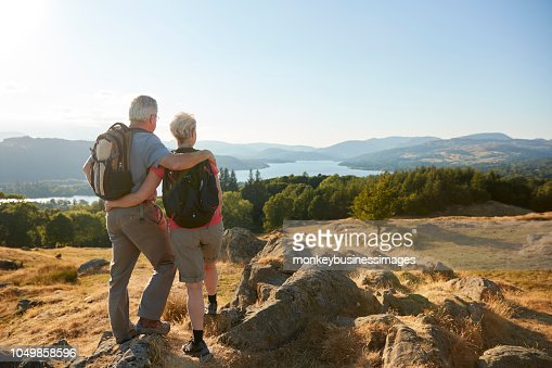 Rear View Of Senior Couple Standing At Top Of Hill On Hike Through Countryside In Lake District UK : Stock Photo