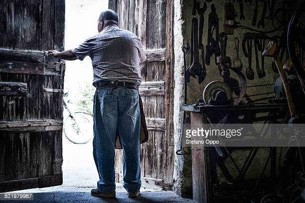 Rear view of senior male blacksmith in opening doors of traditional barn, Cagliari, Sardinia, Italy