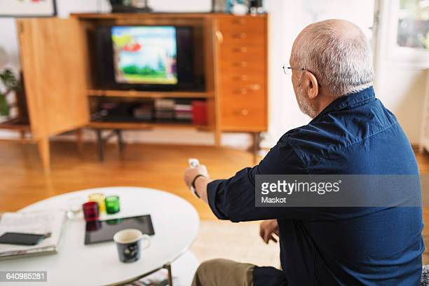 Rear view of senior man changing channels at home