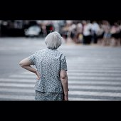 Rear View Of Senior Woman Standing With Hand On Hip At Zebra Crossing