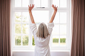 Rear View Of Senior Woman Stretching In Front Of Bedroom Window