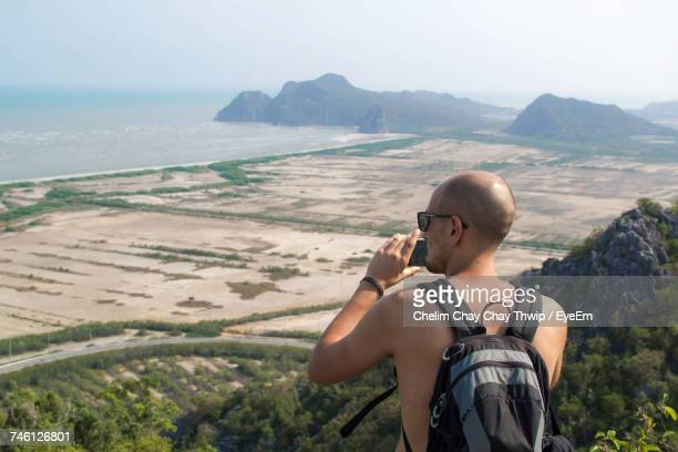 Rear View Of Shirtless Backpack Man Photographing On Top Of Mountain