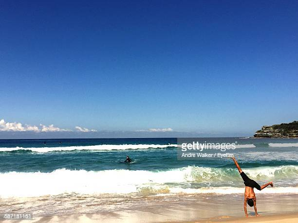 Rear View Of Shirtless Man Doing Handstand At Beach