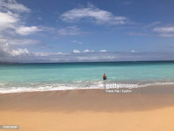 Rear View Of Shirtless Man In Sea Against Cloudy Sky During Sunny Day