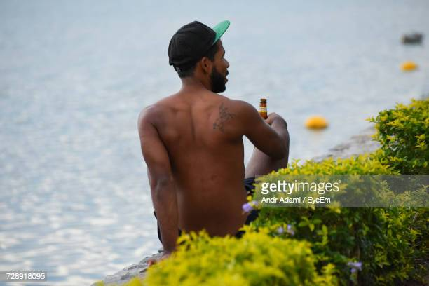 Rear View Of Shirtless Man Sitting By Sea With Beer Bottle