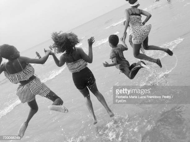 Rear View Of Siblings Jumping At Seashore