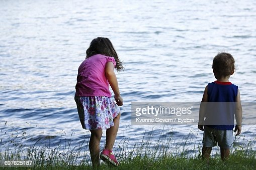 Rear View Of Siblings Standing On Grassy Field Against Lake