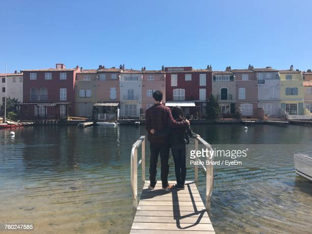 Rear View Of Siblings Standing On Jetty Over Lake In City Against Clear Blue Sky