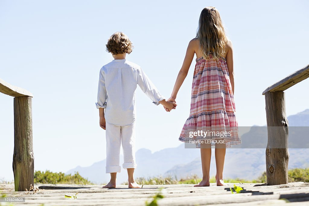 Rear view of siblings standing together at a pier : Stock Photo