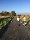 Rear View Of Siblings Walking On Country Road Against Sky