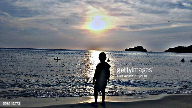 Rear View Of Silhouette Boy At Beach During Sunset