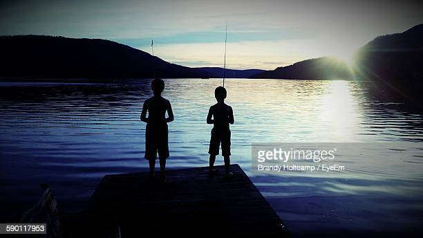 Rear View Of Silhouette Boys Fishing Against Lake During Sunset