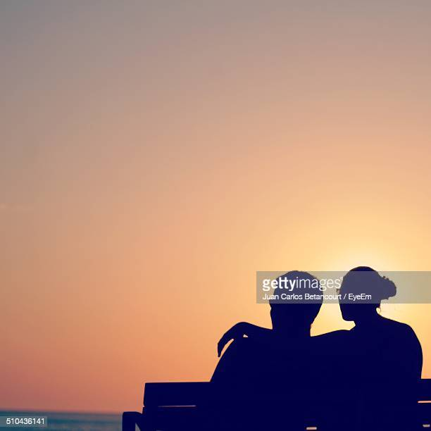 Rear view of silhouette couple sitting on bench against clear sky