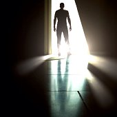 Rear View Of Silhouette Man Standing Against Light At Doorway