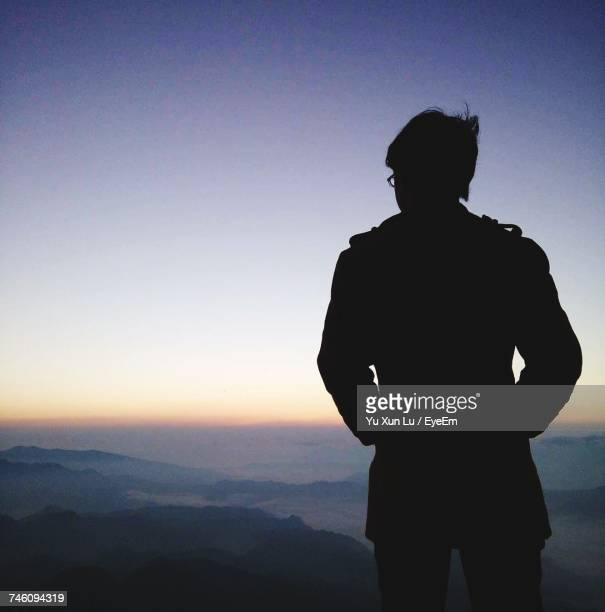 Rear View Of Silhouette Man Standing On Mountain Against Sky At Dusk