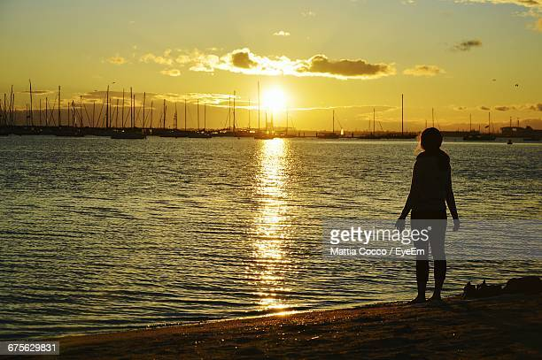 Rear View Of Silhouette Woman Standing At St Kilda Beach During Sunset