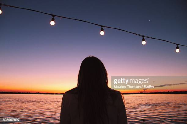 Rear View Of Silhouette Woman Standing In Front Of Sea At Sunset