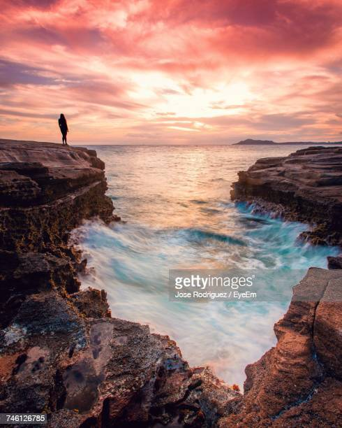 Rear View Of Silhouette Woman Standing On Rock Formation By Sea Against Dramatic Sky During Sunset
