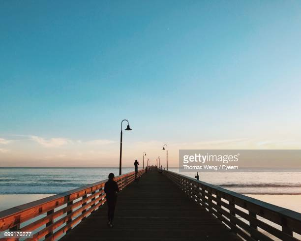 Rear View Of Silhouette Woman Walking On Pier At Beach Against Blue Sky During Sunset