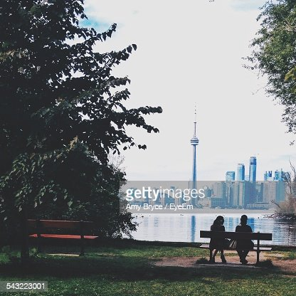 Rear View Of Silhouette Women Looking At Cn Tower And Cityscape Against Sky