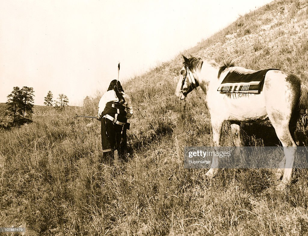 Rear view of Sioux Indian carrying rifle in front of pony 1900