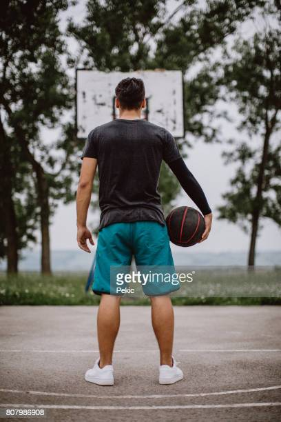 Rear view of sports male holding basketball