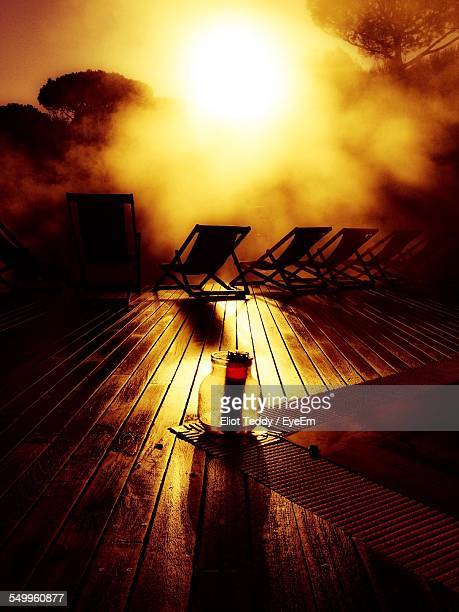 Rear View Of Sun Loungers On Wood Paneled Deck At Sunset