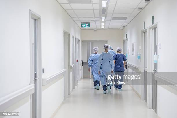 Rear view of surgeons walking down hospital corridor wearing scrubs